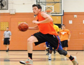 Basketball player dribbling to the basket.