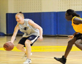 Woman dribbling past another NYC basketball player.