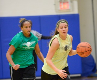 Two women race upcourt in women's basketball league game.