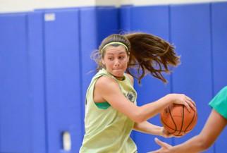 Woman Basketball Player driving to the basket.