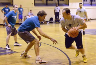 Male player in basketball league playing tight defense.