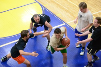 Player goes between defendants in Nyc Summer Basketball League game