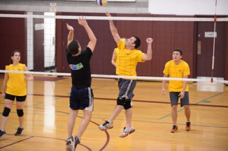 Player in yellow spikes in volleyball league game