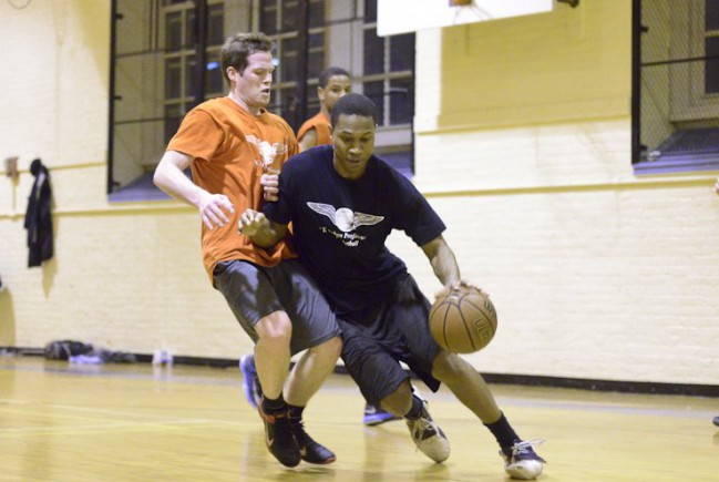 Player in Blue dribbles past defender In Basketball game.