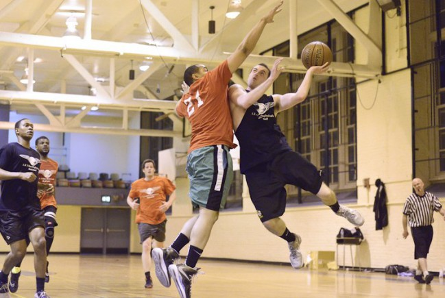 Acrobatic layup in NYC Basketball league game